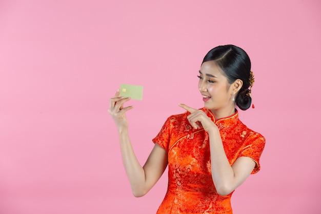 Linda mulher asiática feliz sorri e mostra o cartão de crédito no ano novo chinês em fundo rosa.