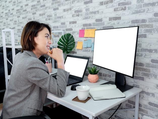 Linda mulher asiática feliz trabalhando com o computador portátil no quarto dela, condomínio.