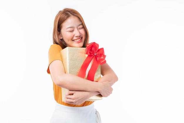 Linda mulher asiática fofa, linda mulher adolescente se sentindo feliz e abraçando uma caixa de presente recebida como um presente de aniversário no fundo branco