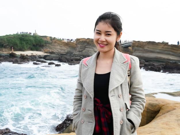 Linda mulher asiática, garota com uma jaqueta de pé e sorrir, tirar uma foto ao lado do mar em sua viagem.