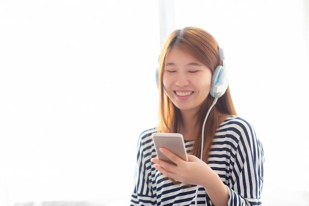 Linda mulher asiática gosta de ouvir música com fone de ouvido
