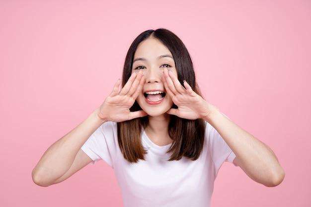 Linda mulher asiática gritando e olhando para cima, usando a boca para dizer algo ou ligar para alguém sobre um fundo rosa.