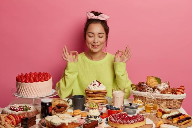 Linda mulher asiática gulosa por doces medita e pratica ioga, come deliciosas panquecas e bolos