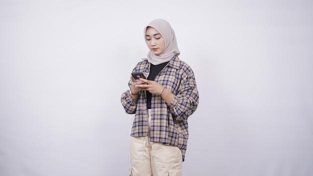 Linda mulher asiática jogando smartphone felizmente isolado no fundo branco