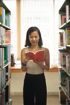 Linda mulher asiática lendo um livro na biblioteca. jovem bibliotecária atraente lendo um livro entre as estantes da biblioteca