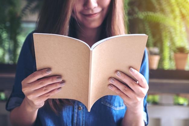 Linda mulher asiática lendo um livro no café moderno