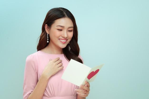 Linda mulher asiática lendo uma carta de amor no dia dos namorados
