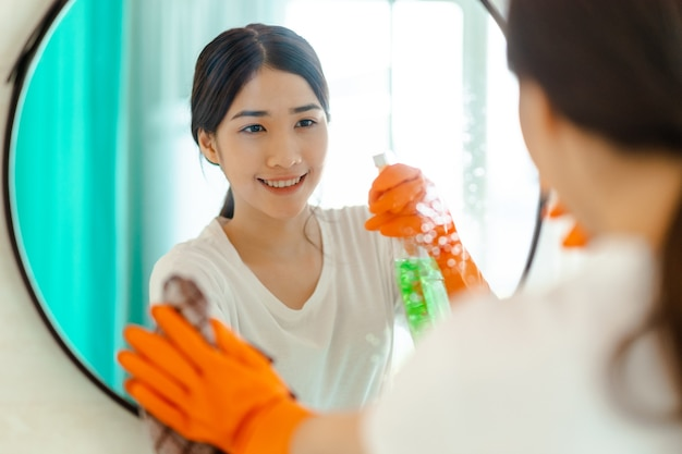 Linda mulher asiática limpando espelho no banheiro