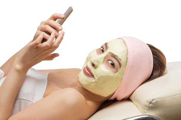 Linda mulher asiática máscara facial usando telefone inteligente.