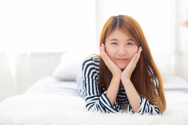 Linda mulher asiática mentindo e sorrir enquanto acorda