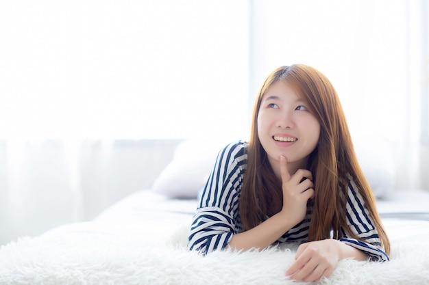 Linda mulher asiática mentindo e sorrir enquanto despertar