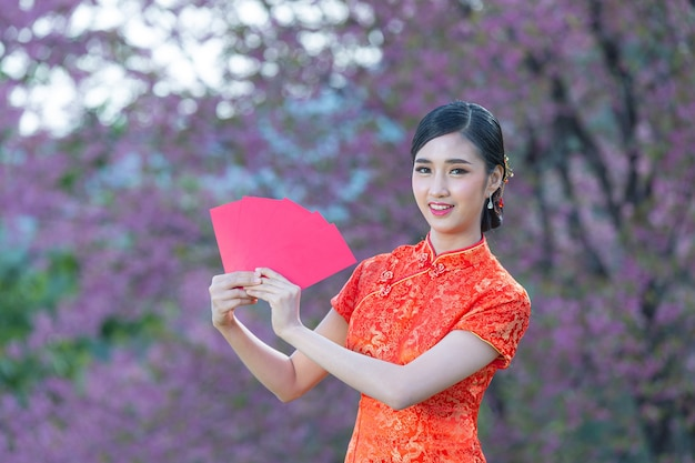 Linda mulher asiática mostra algo e leva envelopes vermelhos no ano novo chinês