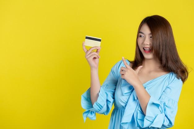 Linda mulher asiática mostrando cartão de crédito na parede amarela