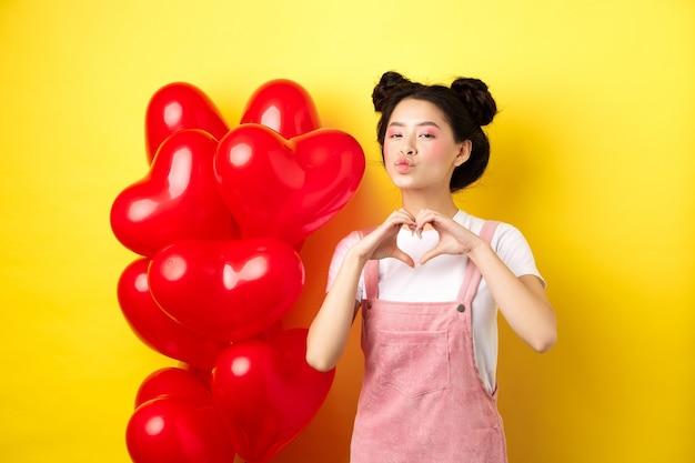 Linda mulher asiática mostrando o coração, eu te amo gesto e beijando os lábios, em pé perto de românticos balões vermelhos. conceito de dia dos namorados.