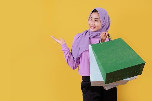Linda mulher asiática mostrando sacolas de compras, vestindo camiseta roxa alegre e alegre