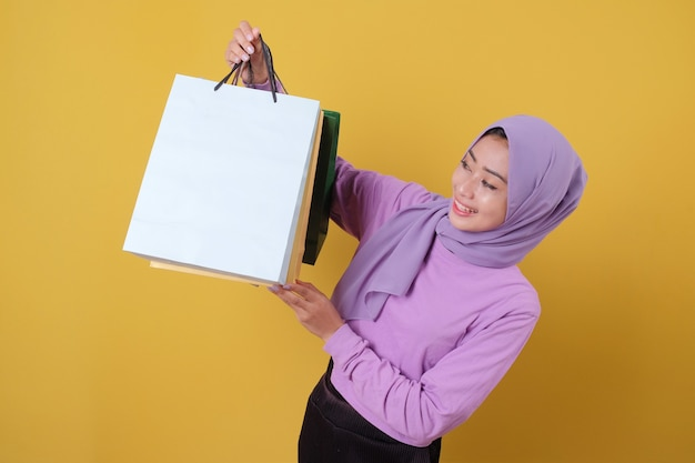 Linda mulher asiática mostrando sacolas de compras, vestindo camiseta roxa