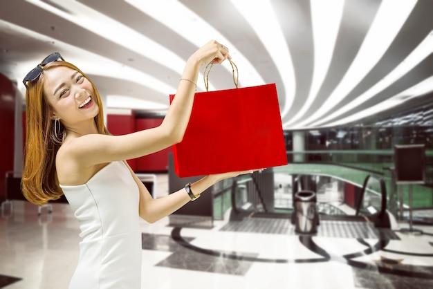 Linda mulher asiática mostrando seus sacos de compras no shopping