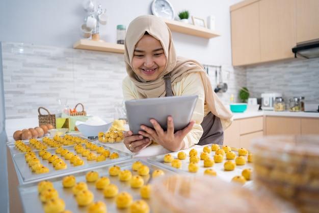 Linda mulher asiática muçulmana fazendo bolo de nastar em casa