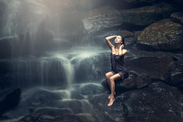 Linda mulher asiática na cachoeira