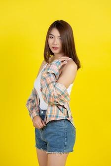 Linda mulher asiática na parede amarela