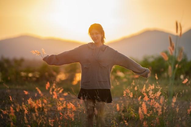 Linda mulher asiática nos campos, sendo feliz ao ar livre sobre o pôr do sol. felicidade saúde liberdade.