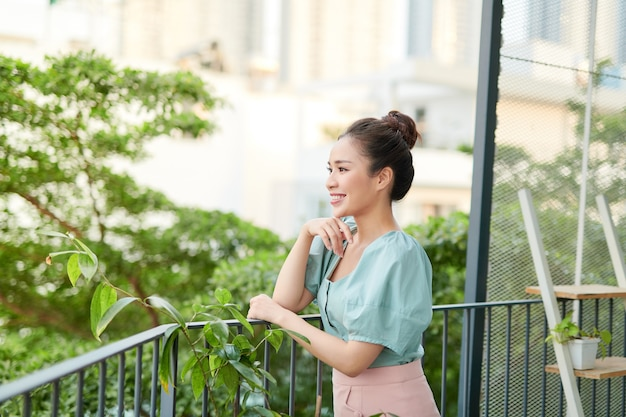 Linda mulher asiática olhando a vista de uma varanda