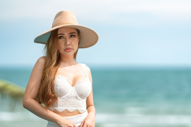 Linda mulher asiática ou tailandesa, ela usa um vestido branco, relaxe na praia para viajar no conceito de verão