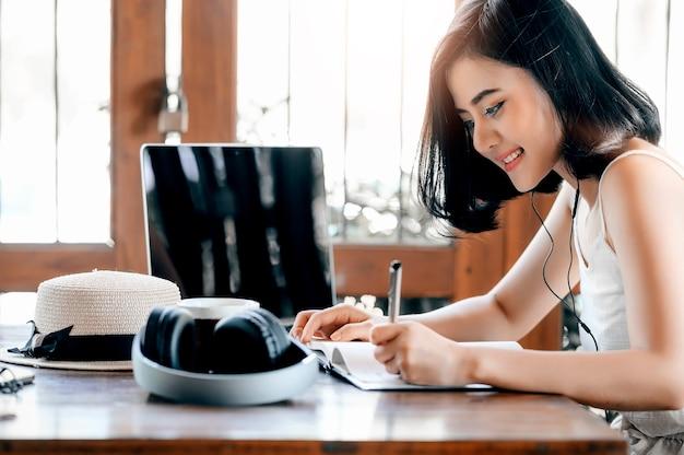 Linda mulher asiática ouvindo música e escrevendo no notebook