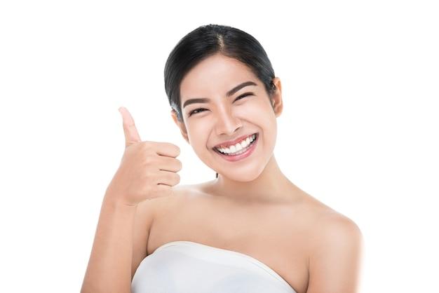 Linda mulher asiática pele perfeita aparecendo polegares isolado com traçado de recorte