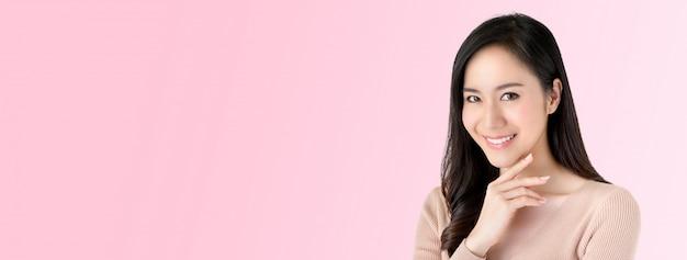 Linda mulher asiática radiante, sorrindo com a mão no queixo