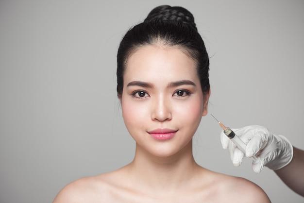 Linda mulher asiática recebe injeções faciais de beleza. injeção de envelhecimento facial.