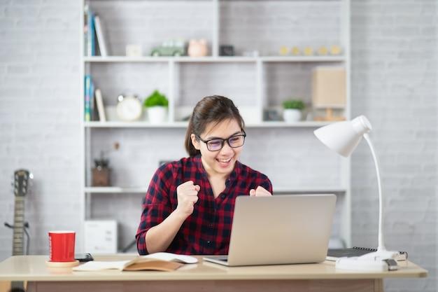Linda mulher asiática relaxando usando o computador laptop enquanto está sentado na mesa. garota criativa trabalhando e digitando no teclado em casa. conceito de trabalho em casa