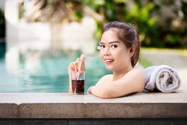 Linda mulher asiática relaxante com bebida