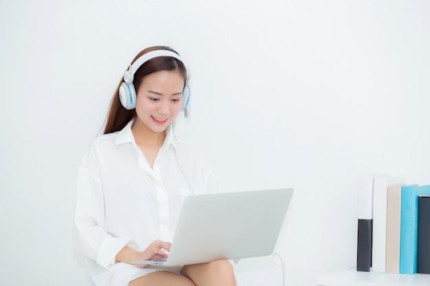 Linda mulher asiática relaxar com desgaste auscultadores desfrutar de ouvir música usando laptop