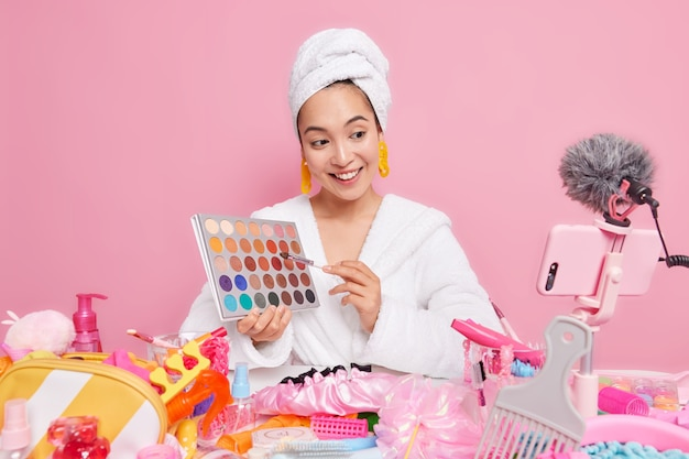 Linda mulher asiática satisfeita segurando paleta de sombras e vai fazer conversas de maquiagem com os seguidores