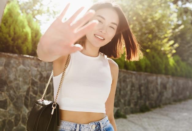 Linda mulher asiática se cobrindo da câmera e sorrindo, posando com uma roupa da moda, caminhando no parque