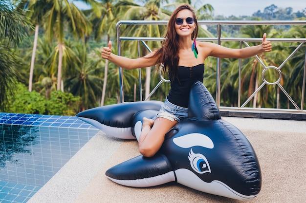 Linda mulher asiática se divertindo na piscina em uma villa tropical nas férias de verão na tailândia, brincando com uma grande orca vestindo maiô preto e óculos escuros, corpo sexy, positivo mostrando os polegares para cima