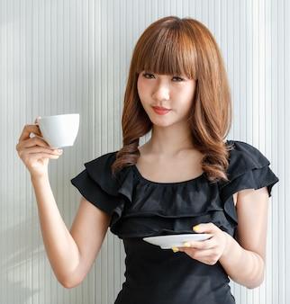Linda mulher asiática segurando a xícara de café branco, ela olhando para a câmera, conceito para o intervalo, copie o espaço à esquerda.