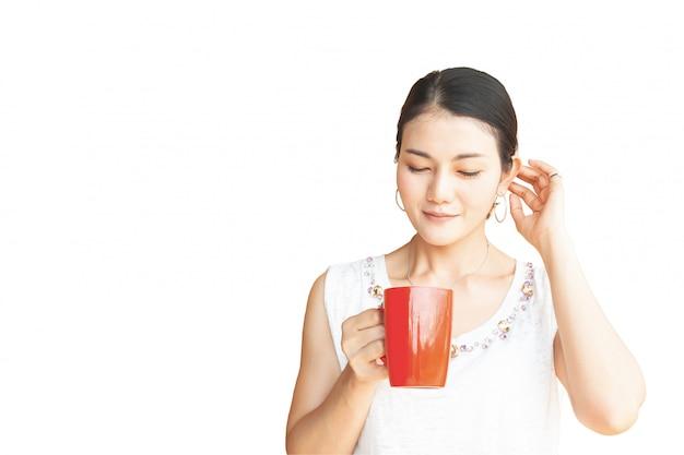 Linda mulher asiática segurando caneca vermelha