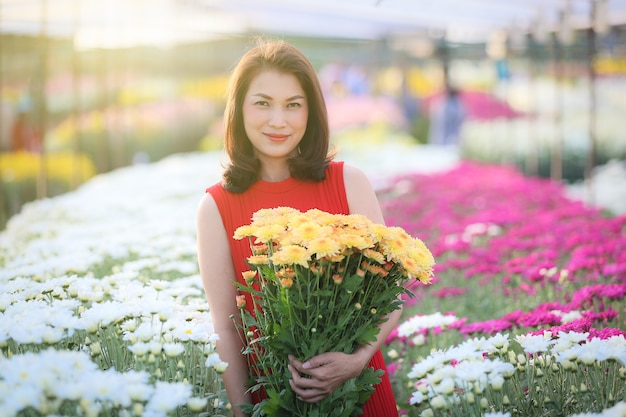 Linda mulher asiática segurando flores amarelas nas mãos com maneira de orgulho, proprietário do jardim de flores satisfeito com flores de boa qualidade para venda.