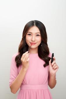 Linda mulher asiática segurando gloss vermelho e aplicando-o