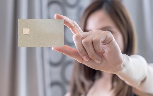 Linda mulher asiática segurando o cartão de crédito em branco dourado