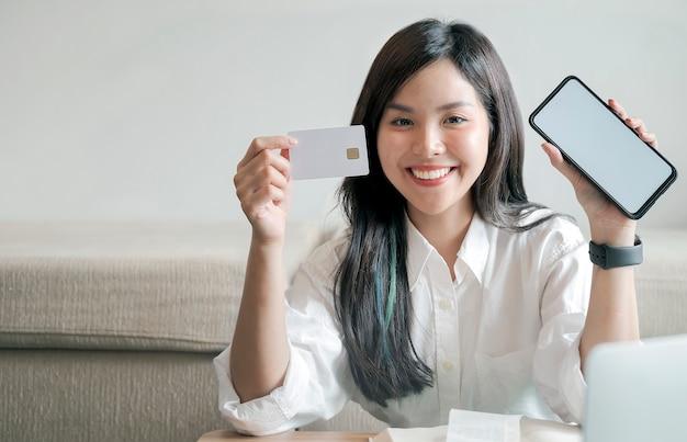 Linda mulher asiática segurando o cartão de crédito em branco e smartphone.