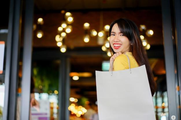 Linda mulher asiática segurando o saco de compras no centro comercial de departamento
