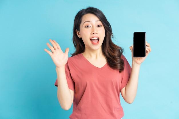 Linda mulher asiática segurando o smartphone na mão com uma expressão alegre