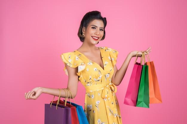 Linda mulher asiática segurando sacolas coloridas