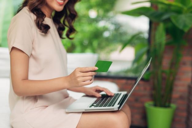 Linda mulher asiática segurando um cartão de crédito e fazendo compras online