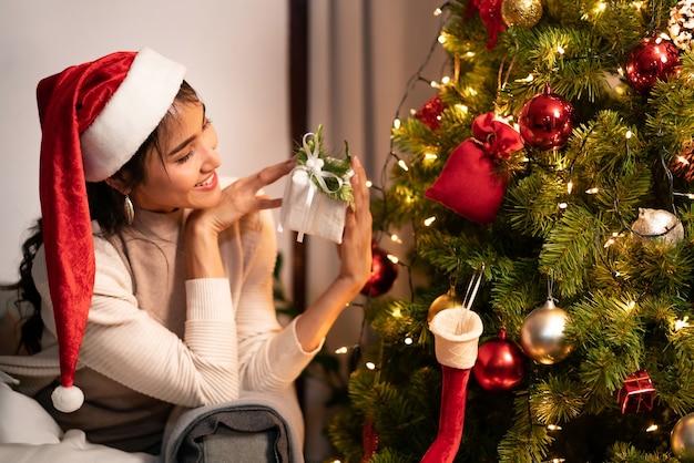 Linda mulher asiática segurando um enfeite de natal para decorar a árvore de natal