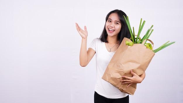 Linda mulher asiática segurando um saco de papel com legumes frescos e muito feliz apontando com a mão e o dedo na superfície branca isolada