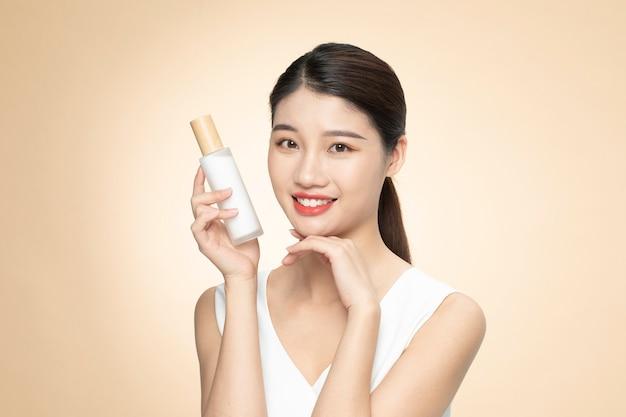Linda mulher asiática segurando uma garrafa de produto em um fundo laranja Foto Premium